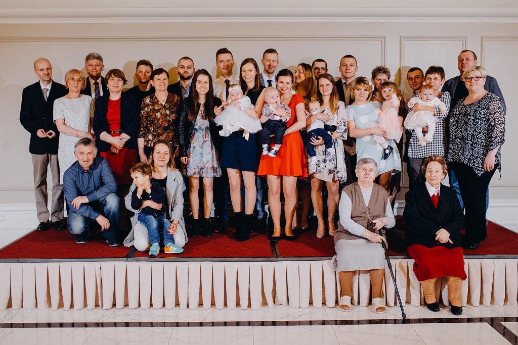 Grupowe zdjęcie na chrzcinach, gdzie na fotografii jest cała rodzina